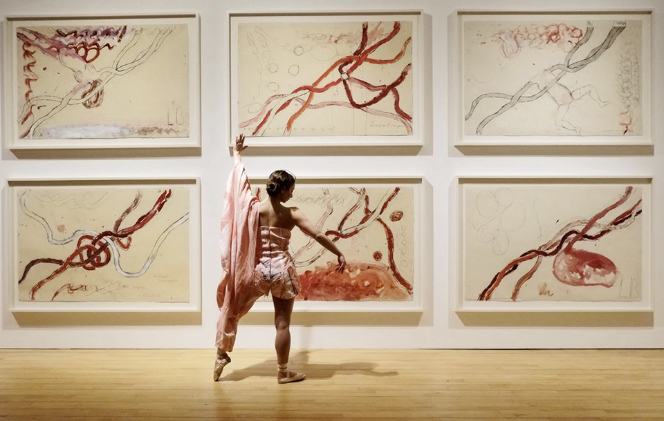 Photo of a ballerina in front of artworks