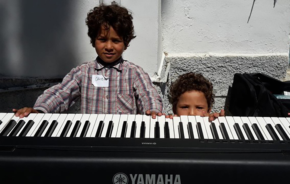 Two children learning how to play music and communicate as part of the Windows on the World project, helped by Dee Isaacs