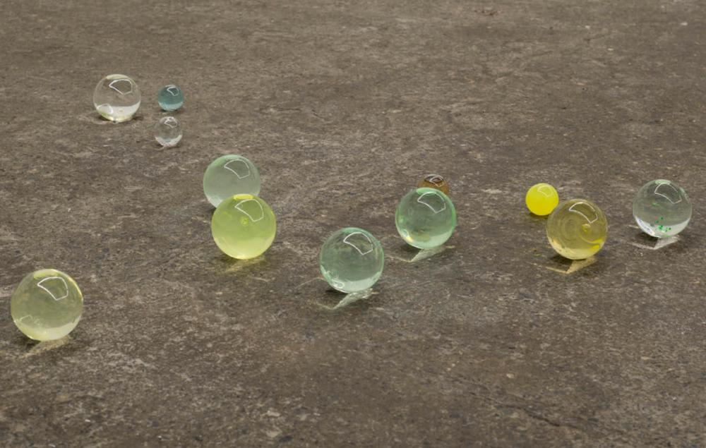 Hand-blown glass marbles filled with soluble and non-soluble ink, found liquids, split multi-channel audio, light reflections, 2016