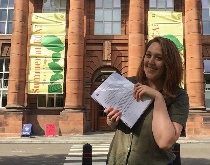 Photography of Carley Winiesdorffer in front of Edinburgh College of Art Main Building holding there dissertation..
