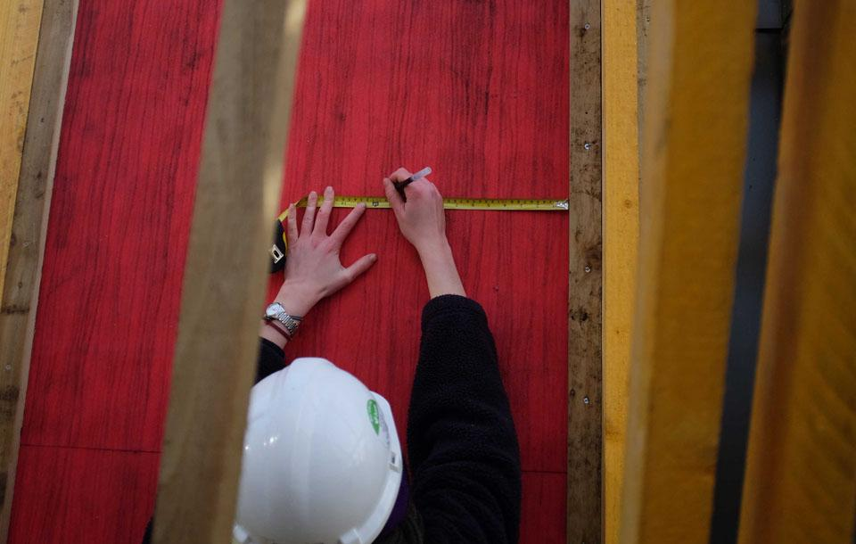 Photo of a student measuring cladding