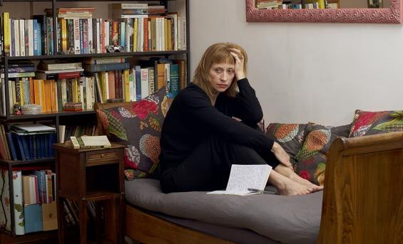 Woman sits on sofa in front of book shelf