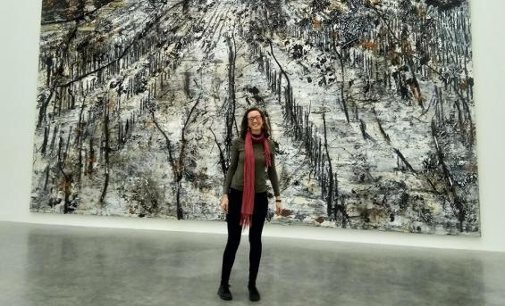 Photograph of Genevieve Fay stood in front of large work by Anselm Kiefer at the White Cube gallery in London.