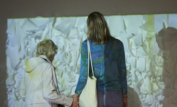 Photo of two people holding hands in front of an artwork